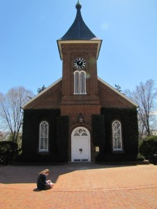 A shot from the front of Lee Chapel with red bricks in the foreground and a girl sitting on a step