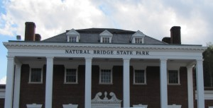 "a red brick building with white pillars and ""Natural Bridge State Park"" across the top"