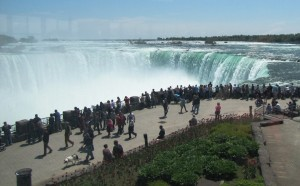 Niagara Falls and a number of people walking and standing along the walkway next to it