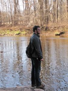 man standing on creek bank