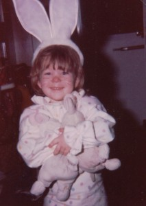 small child dressed in polka dot outfit and weraing bunny ears holding two stuffed bunnies