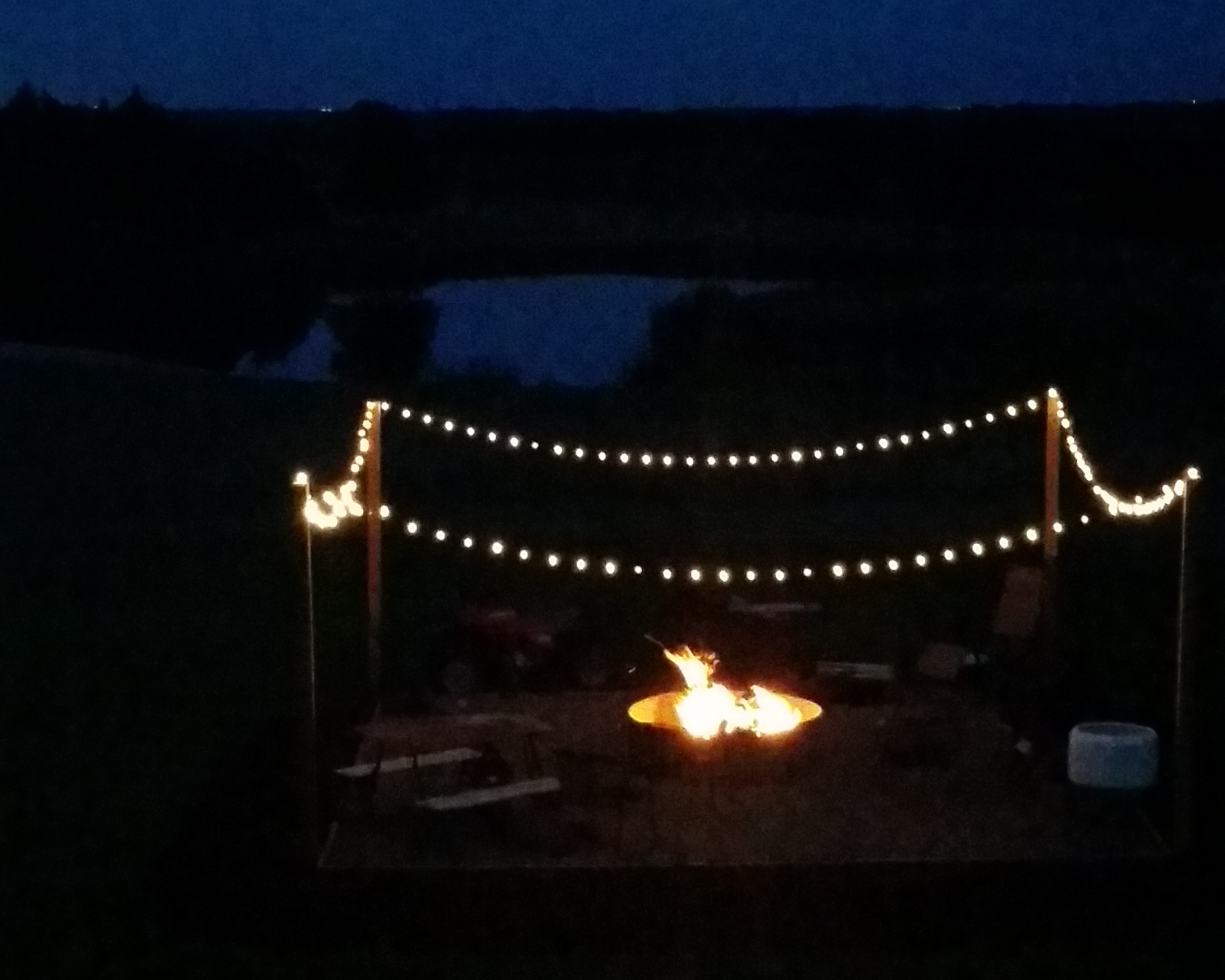 a firepit in the dark surrounded by a square of lights